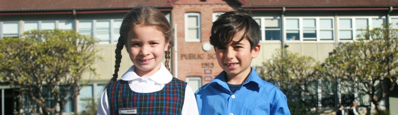 Two students standing in front of school